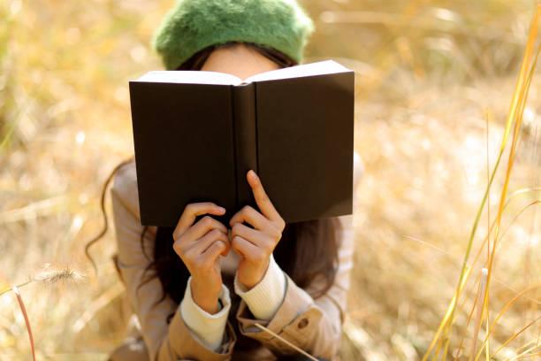 Jeune femme qui lit un livre dans un champ de blé