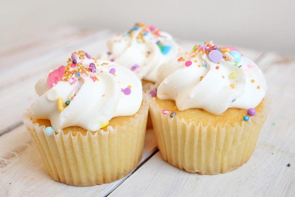 Trois cupcakes sur une table en bois blanc