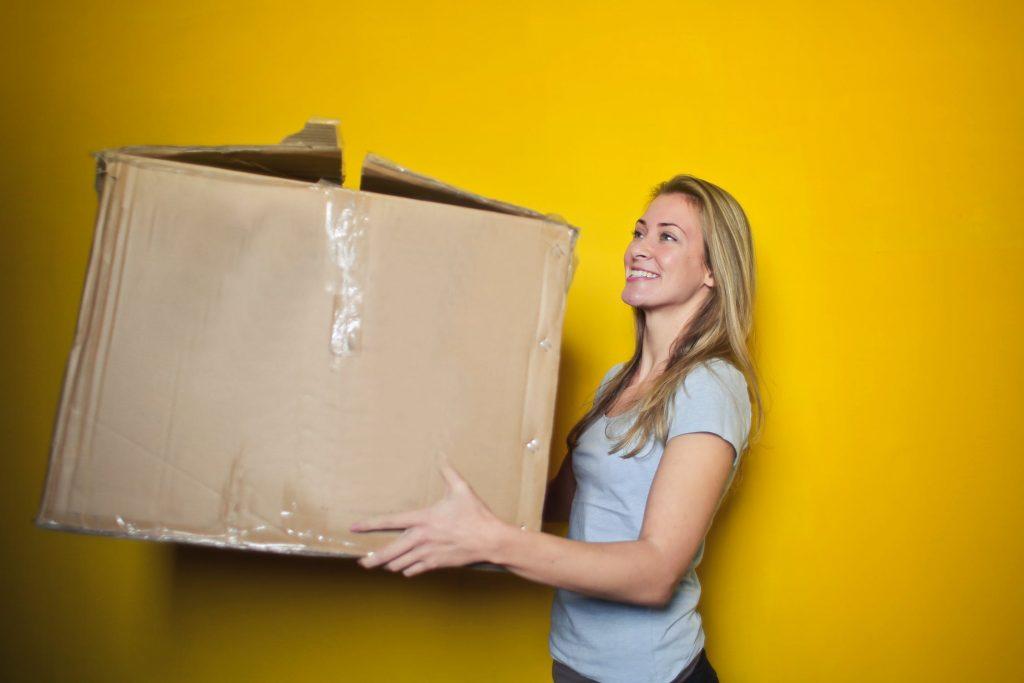 Jeune femme qui porte un gros carton de déménagement