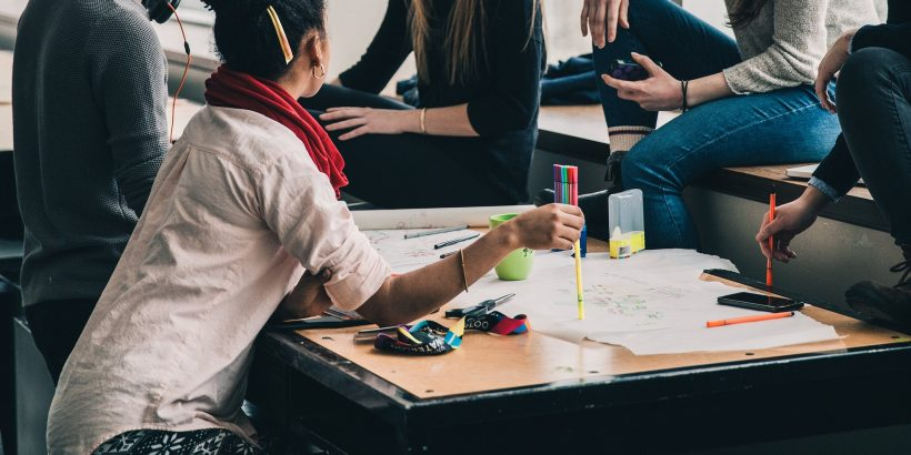 Groupe d'étudiants assis autour d'une table en train de travailler