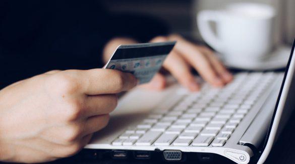 personne qui paye ne ligne carte bancaire a la main et clavier d'ordinateur