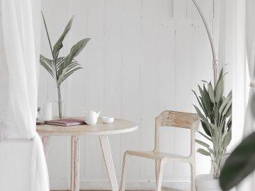 pièce en parquet clair avec table et chaise blanches et luminaire design