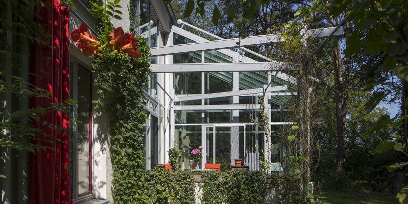 Véranda construite le long d'une maison et au beau milieu d'un jardin