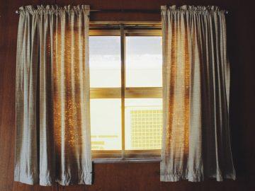 rideaux gris accorchés à des petites fenêtres