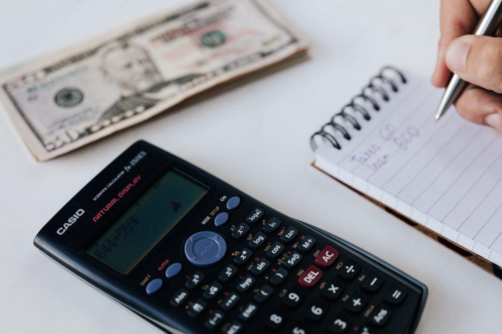 calculatrice posée à côté d'un carnet