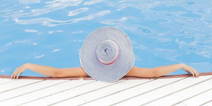 piscine avec une femme dedans avec un chapeau sur la tête